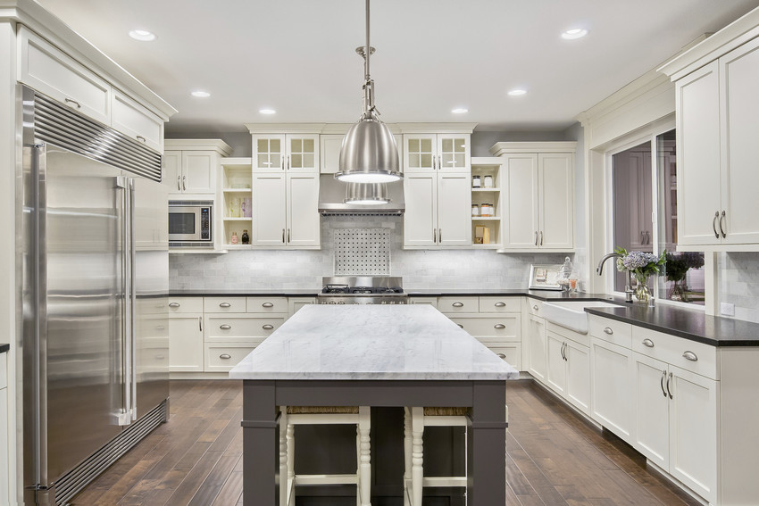 Luxurious kitchen interior with granite countertops, a chrome fridge, and stove.