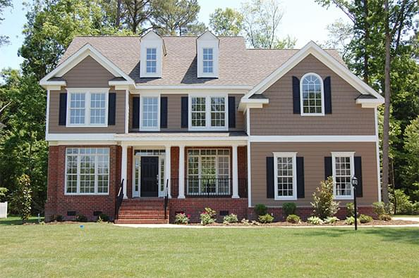 Two-story brick and paneled house with black shutters and white windows.