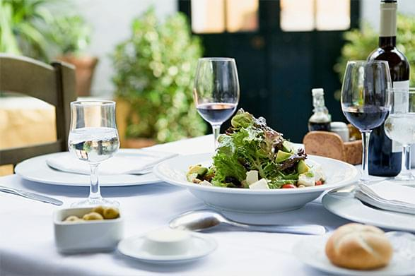 Wine glasses with dinner rolls and salad on a white tablecloth