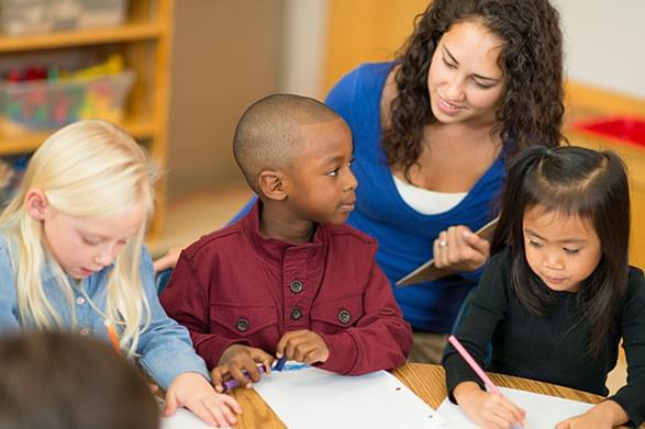 Small children writing with teacher