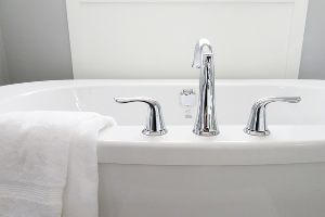A white porcelain bathtub in a bathroom.