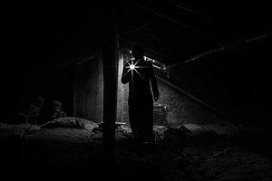 A person holding a flashlight in a dark basement.