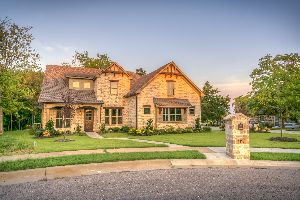 A brick luxury home with a manicured lawn.