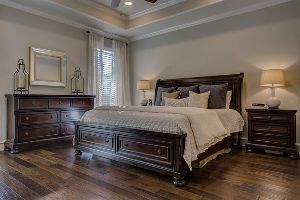A king-sized bed in the middle of a neutrally decorated bedroom with hardwood floors.