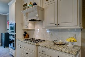 A kitchen with granite countertops, white cabinets, and stainless steel appliances.