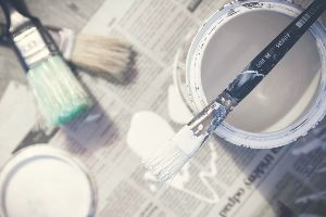 A pail of paint opened and sitting next to various paint brushes.