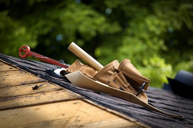 A shingle roof with a tool belt full of roofer tools.