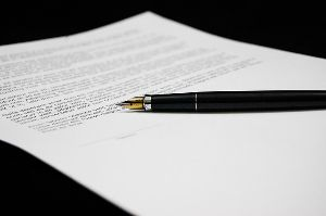 A contract written on a white piece of paper with an elegant fountain pen resting over the signature line.