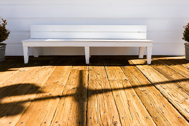 A white bench sitting between two shrubs on a wooden deck.