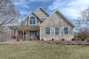 A brown single-family home with a wide front porch and grassy lawn.