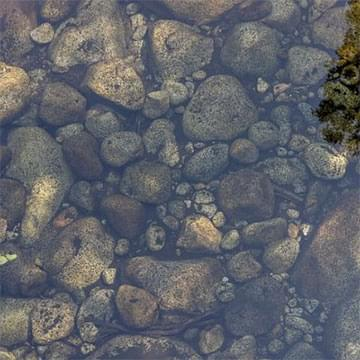 pebbles under clear water