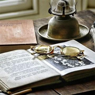 spectacles and an oil lamp with old books