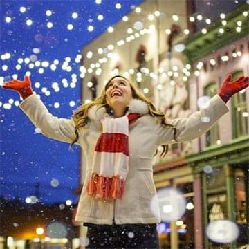 Joyful woman looking up at white lights and snow