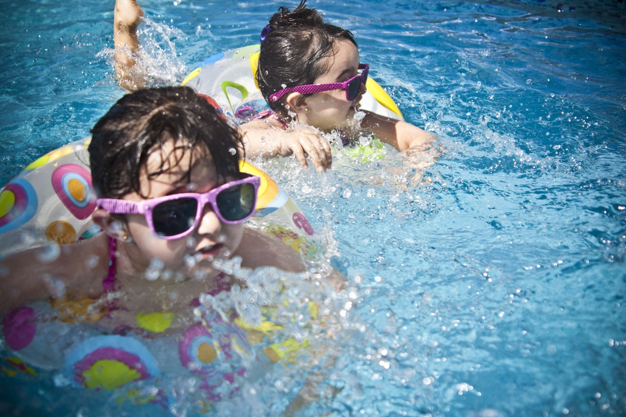 Two young girls swimming in a pool with floaties.