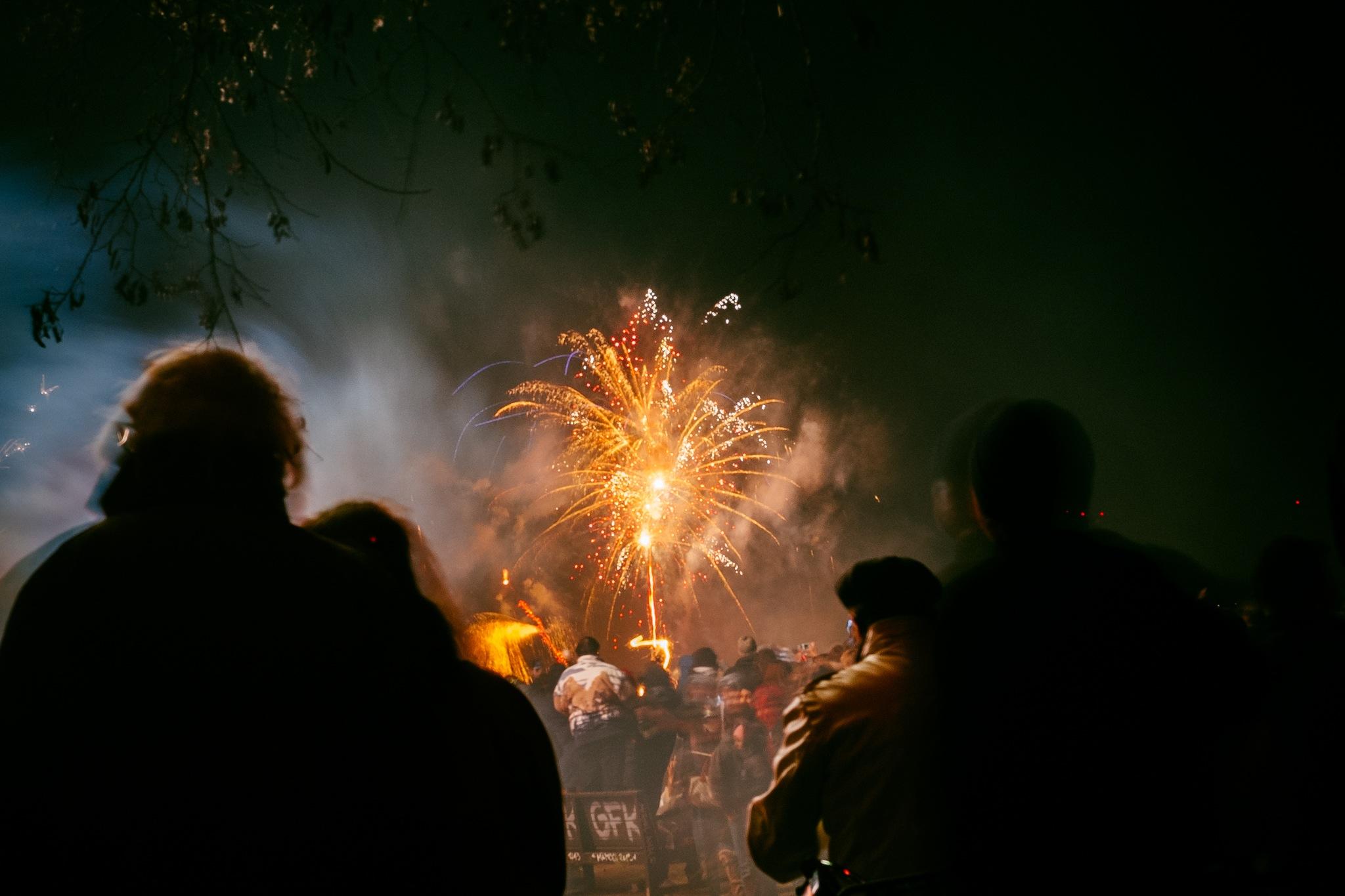 People standing in the dark watching fireworks.