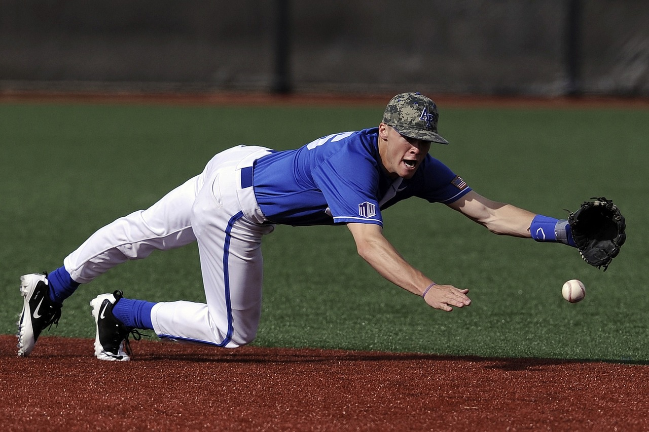 Man in a baseball uniform sliding onto a plate to catch a ball.