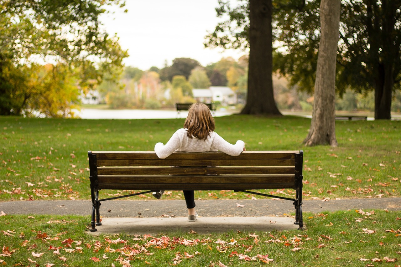 Woman sitting relaxed on a park bench.