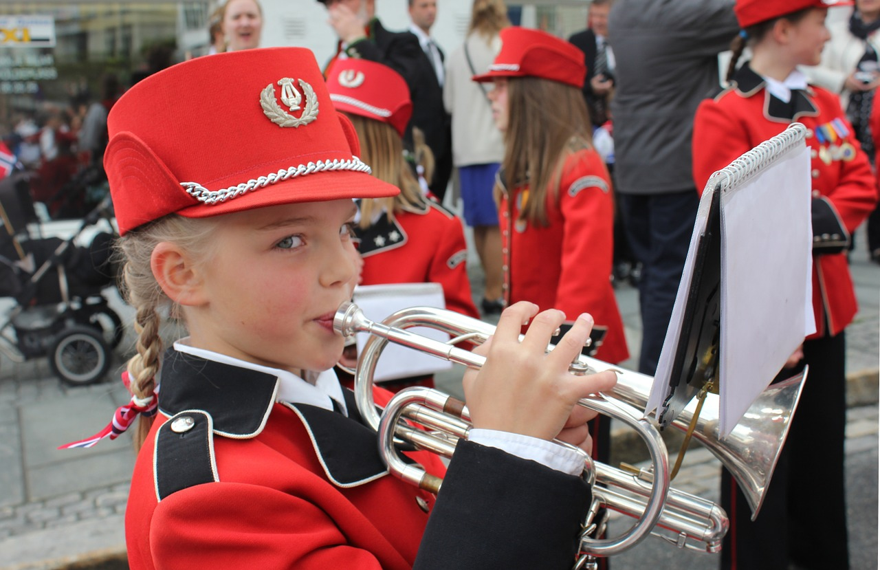 Girl with a band uniform playing the trumpet.