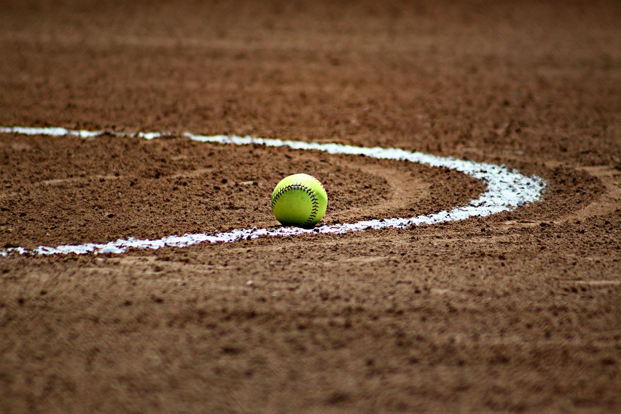 Green softball sitting on a baseball field.
