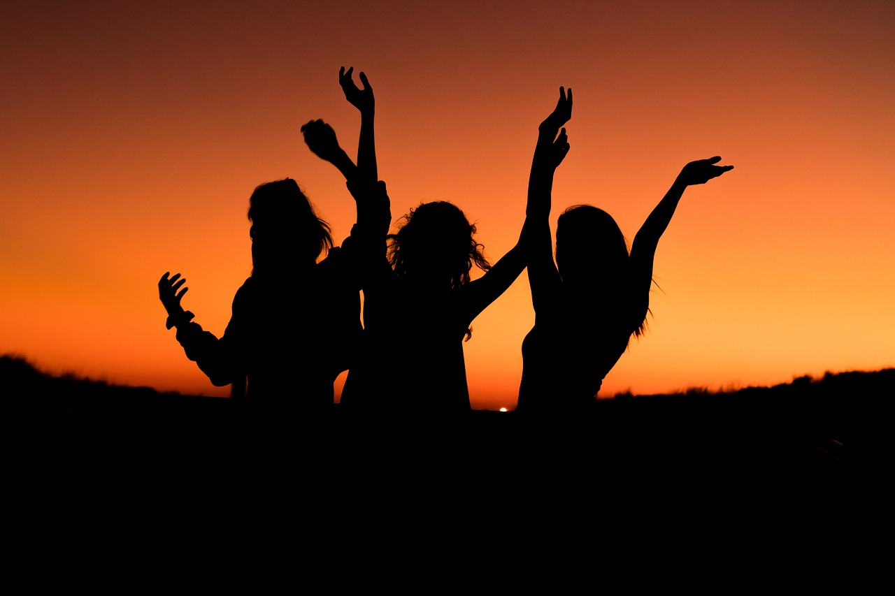 Three silhouettes of happy women set against a sunset.