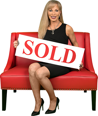 Linda Craft sitting on chair holding sold sign