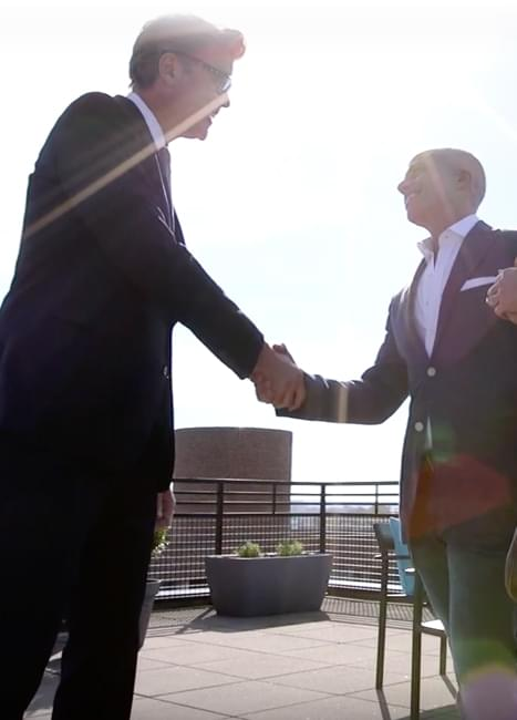 Jeff shaking hands on a rooftop deck with a city view