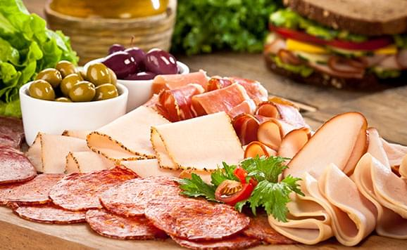 wooden board with cheese and cold cuts