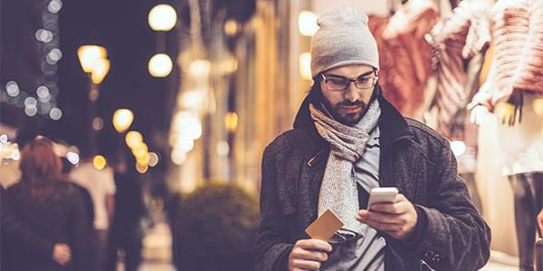 man on a city street holding a business card and looking at a website