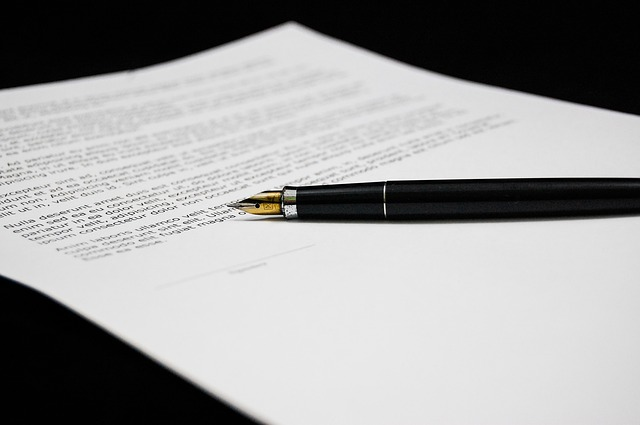 A document written like a contract with a fountain pen resting near the signature.