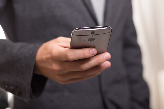 A man wearing a suit and holding a smartphone in his right hand.