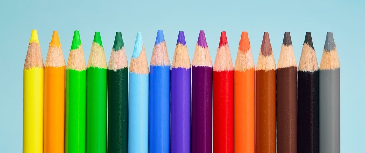 Closeup of colored pencils in all colors of the rainbow lined up with the pencil tips facing up.