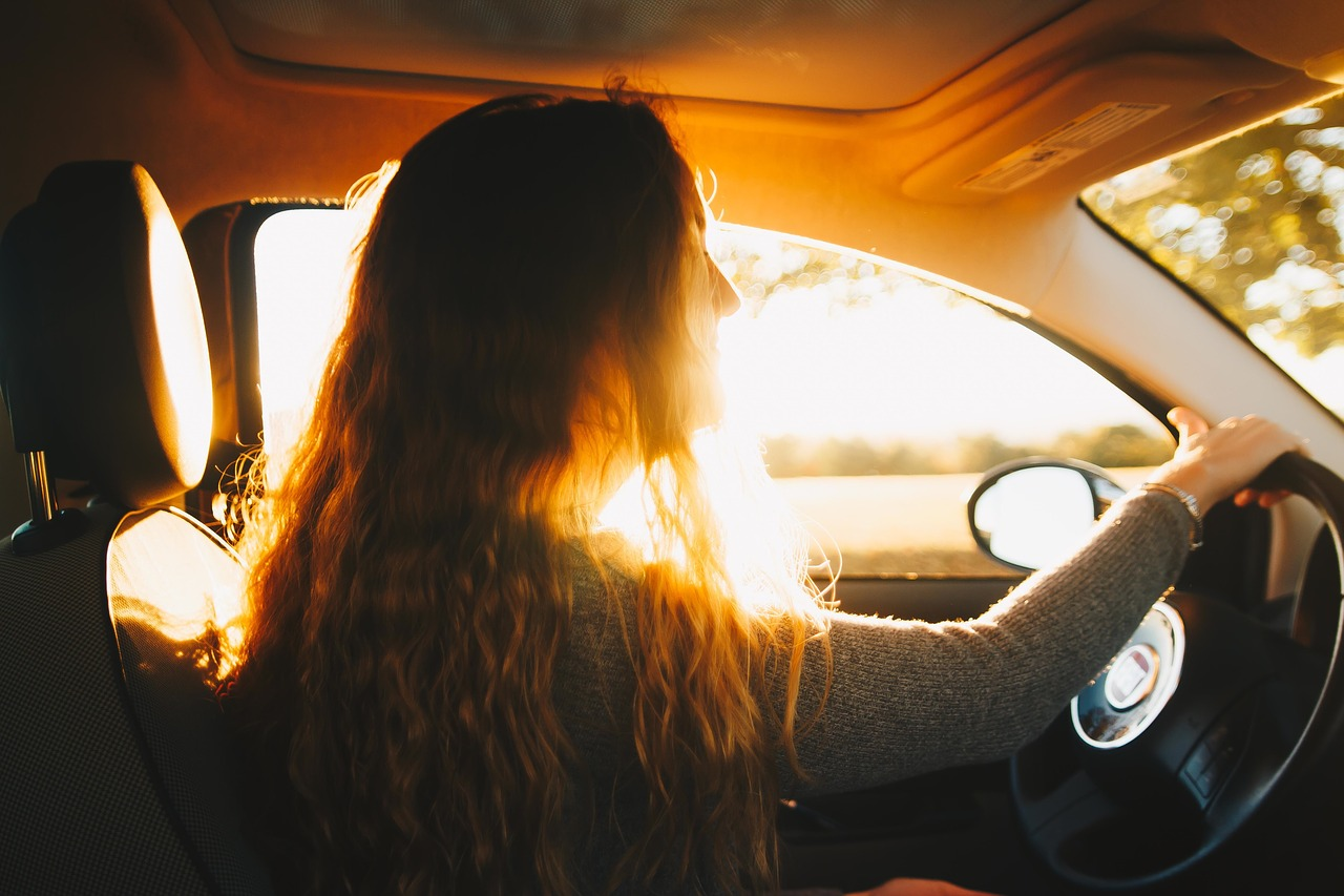 Woman with long hair sitting in the front seat of her car.