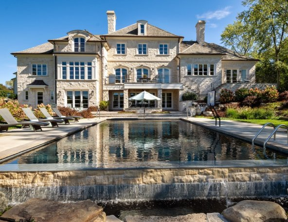 Large stone home with a pool