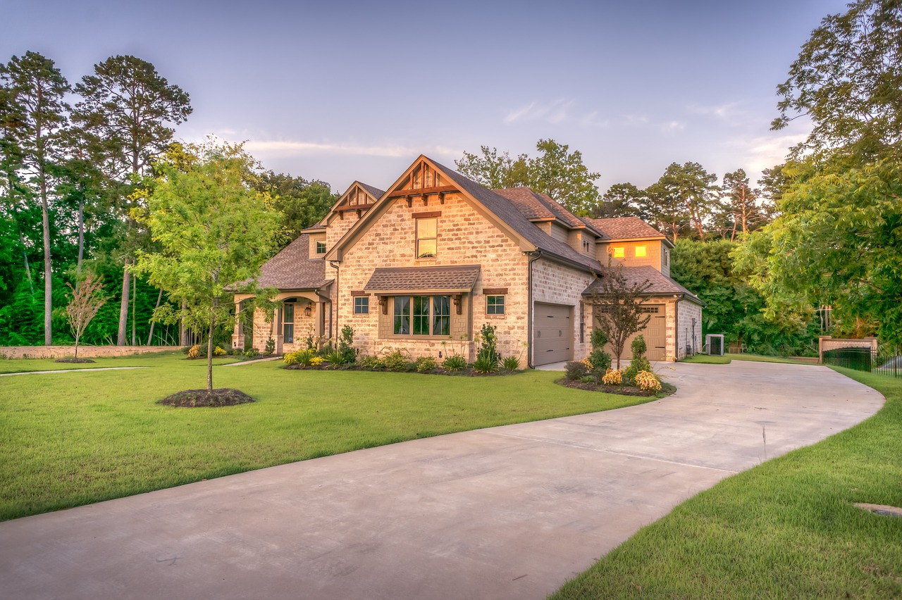 Beautiful brick home with a huge green yard at sunset.