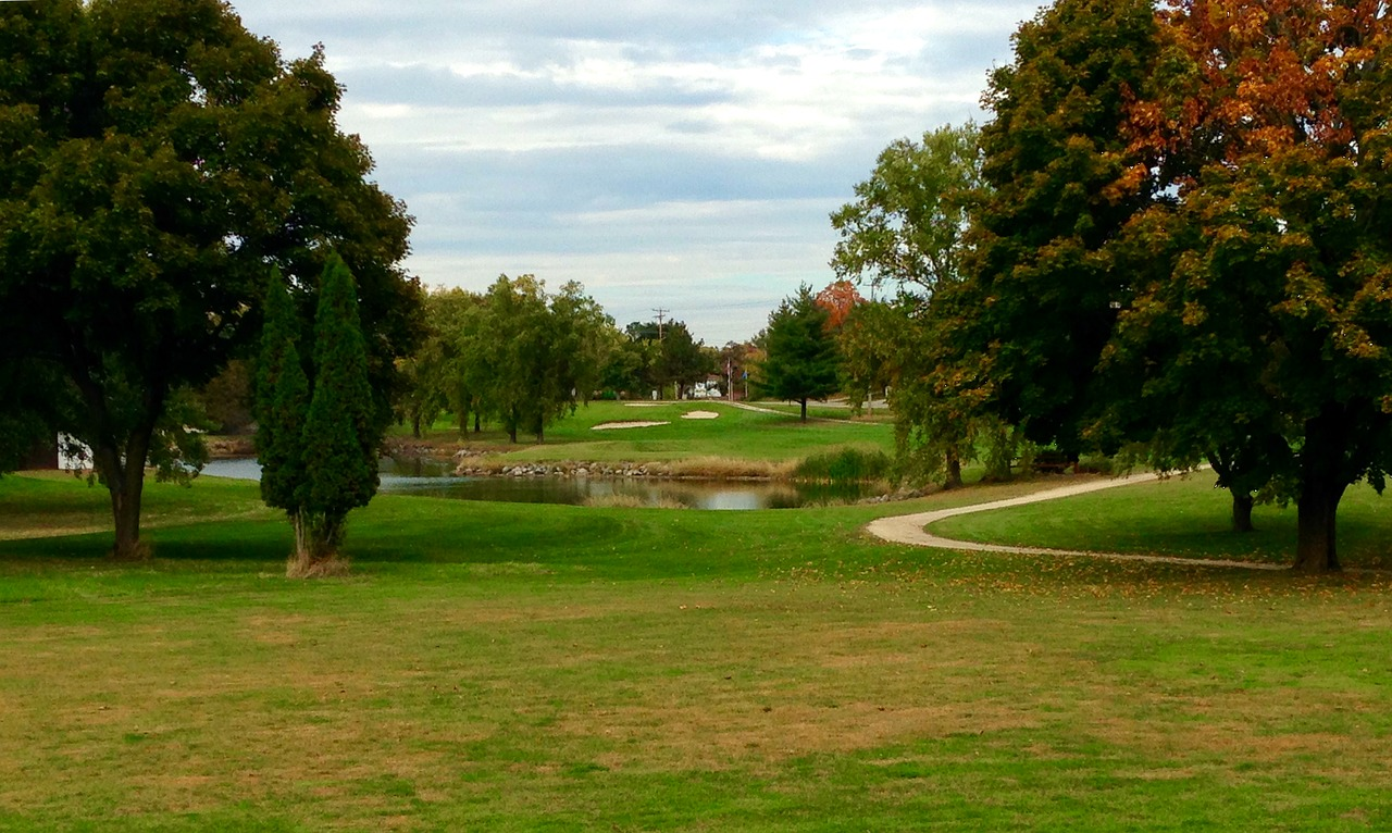Green golf course with red trees.