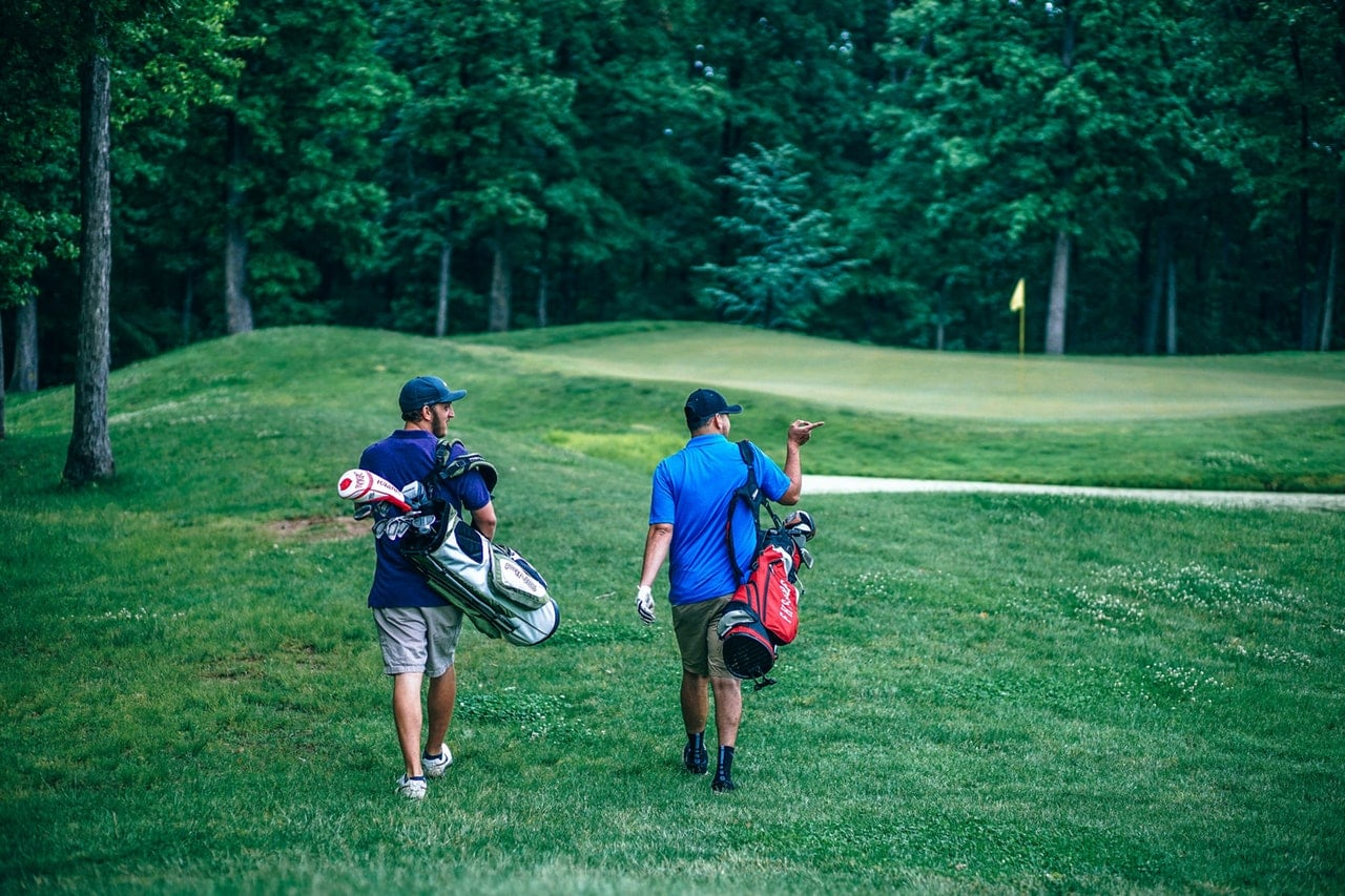 Two men walking across a bright green golf course carrying bags.