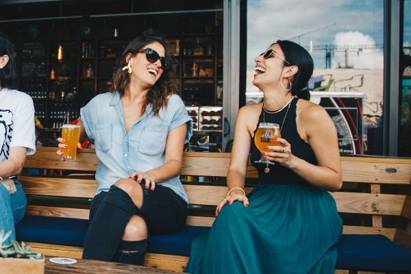 Two friends sitting side by side on a bench, holding amber glasses of beer and laughing.