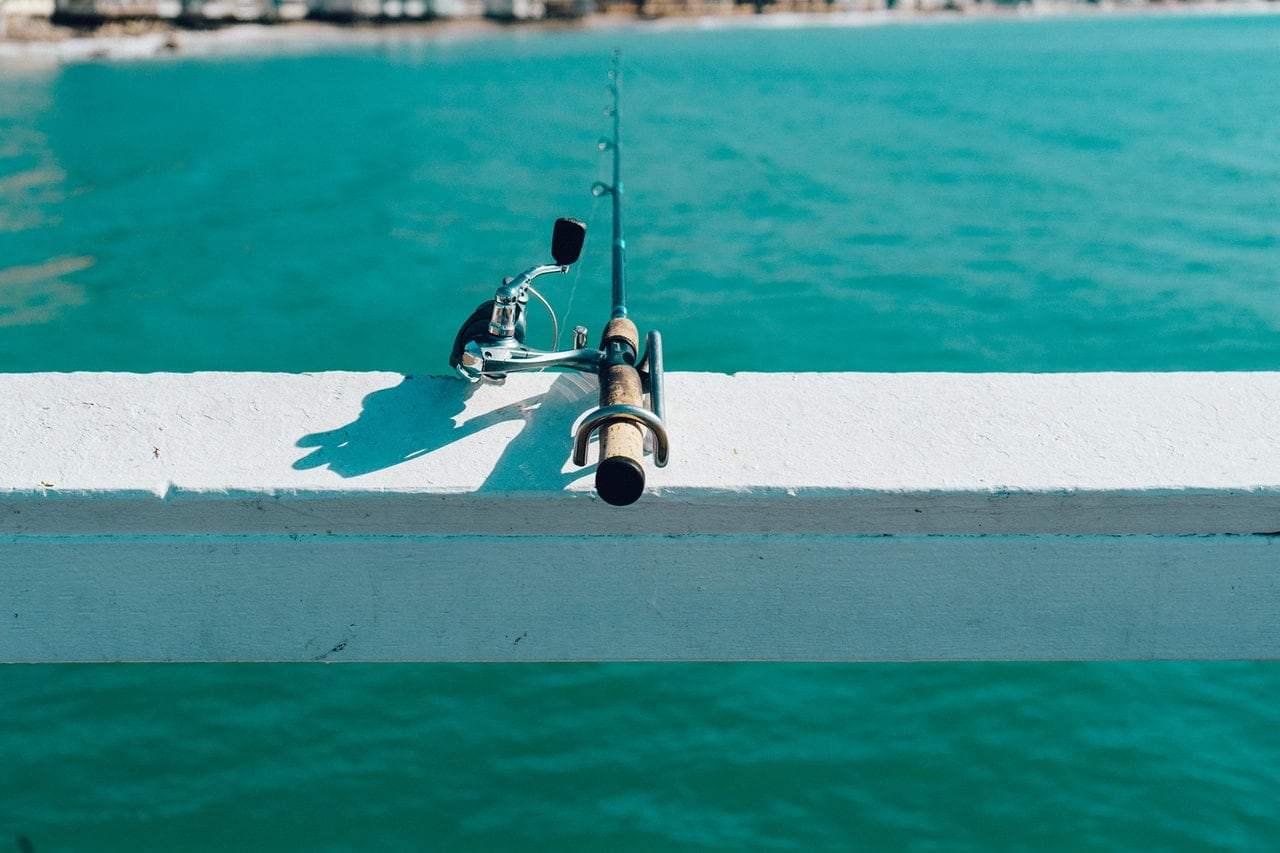 A fishing pole balancing on the edge of a pier.
