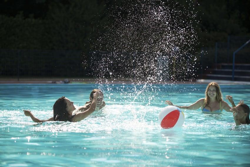 Four kids splashing water in a pool.