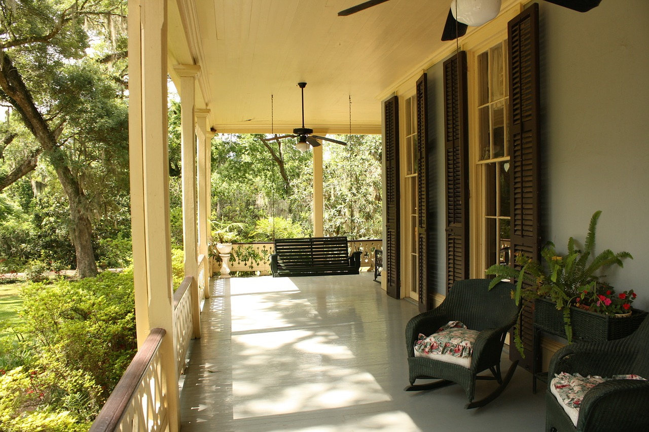 Wraparound porch with a swing and surrounded by ferns on a beautiful southern-style home.