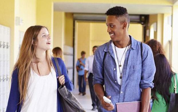 Students talking together in school hallway