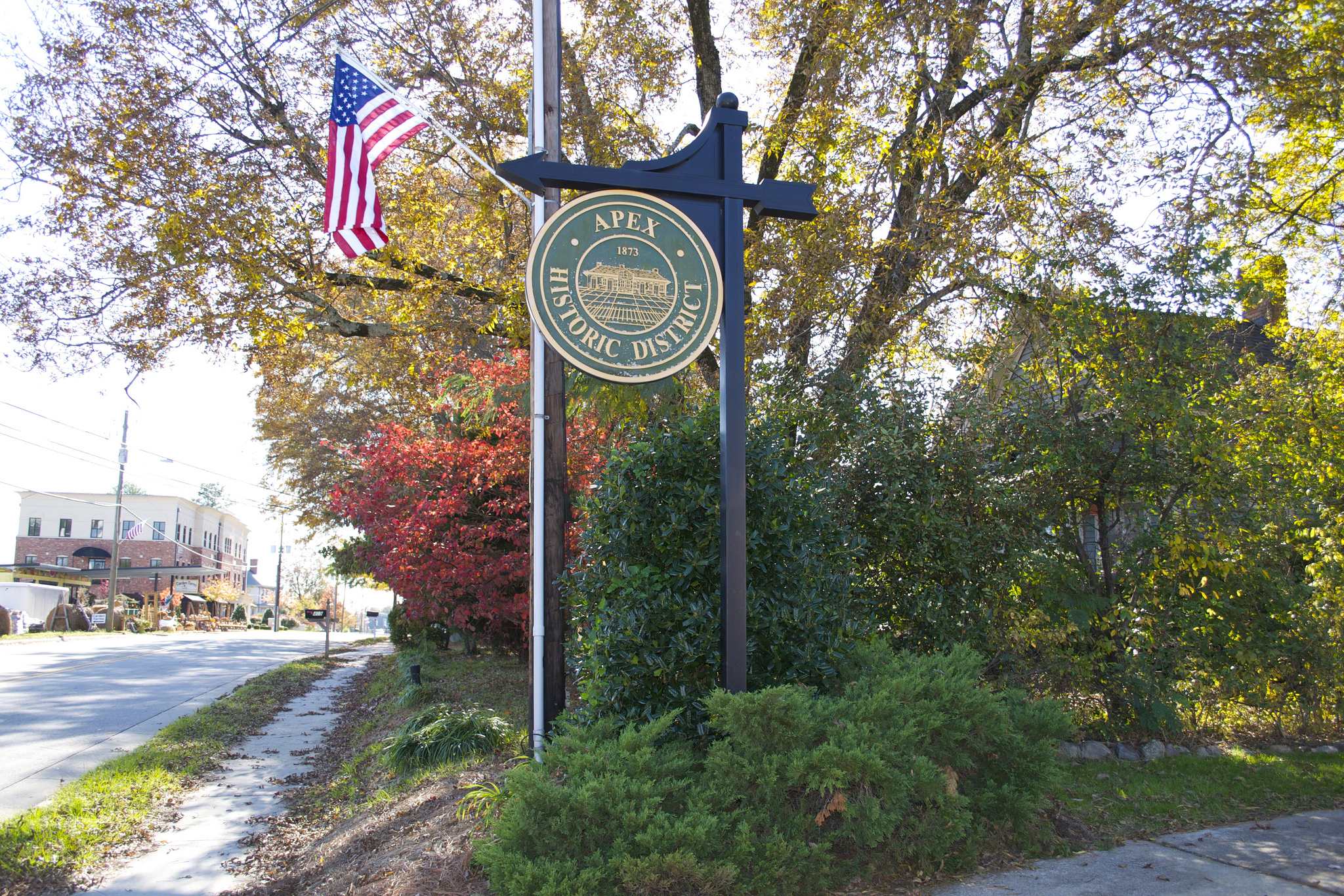 Sign welcoming visitors into the Apex Historic District surrounded by trees and foliage.