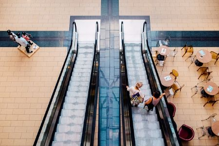 escalators and shoppers in an upscale shopping mall