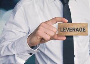 man holding a block with word 'leverage' on it
