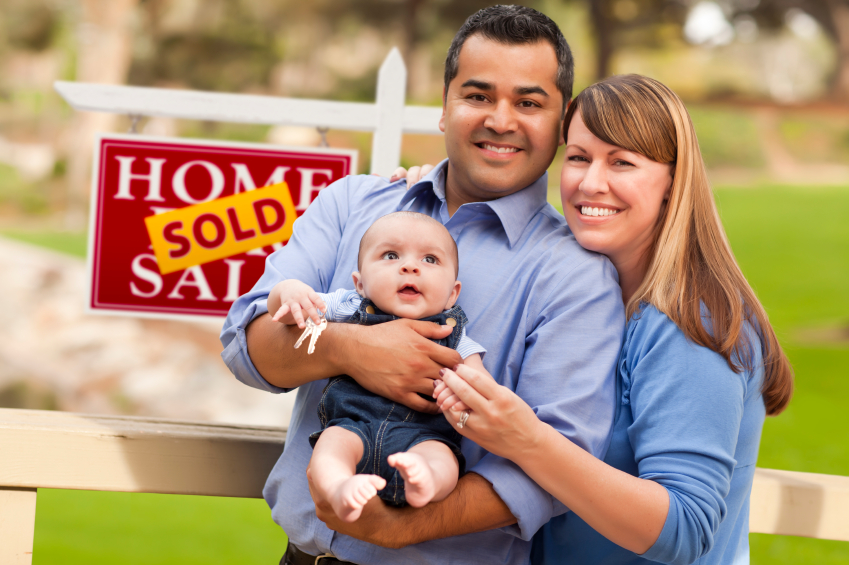 """home sellers beside """"sold"""" sign"""