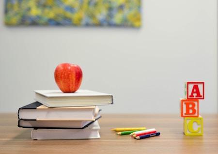 School books, colored pencils, letter block, and apple on a school desk
