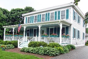 A large single-family home with a wraparound porch and teal green shutters.