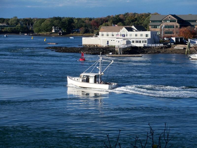 A small fishing boat sailing along Portsmouth Harbor.