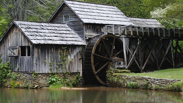 A wooden building with a mill wheel overlooking a still river.