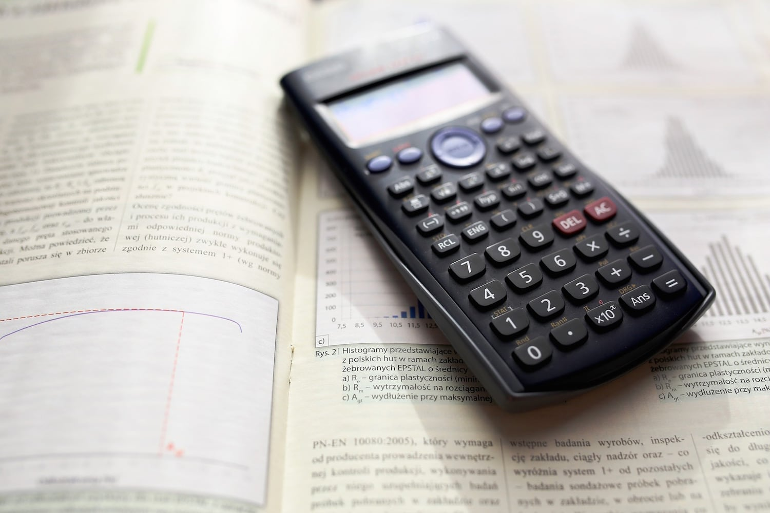 A graphing calculator sitting on an open page in a math textbook.